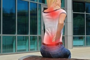 Woman with neck / back pain. Business woman rubbing her painful back. Pain relief concept